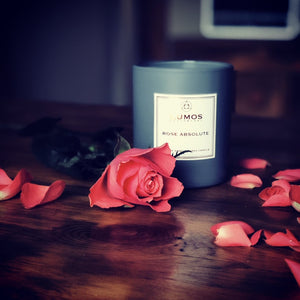 Rose Absolute Scented Soy Wax Candle Subscription UK In A Grey Jar on a wooden background surrounded by rose petals and a single rose