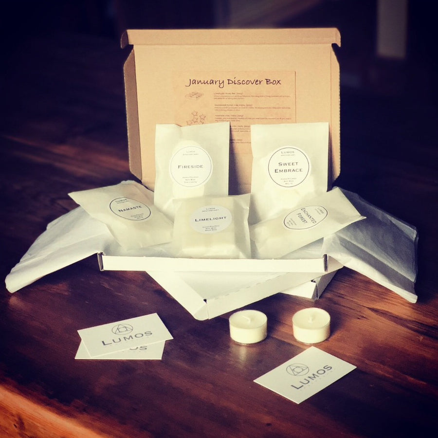 Monthly subscription box. A white cardboard box opened with five bags of wax melts inside. Two tea lights on a wooden table with 3 lumos apothecary cards scattered around it