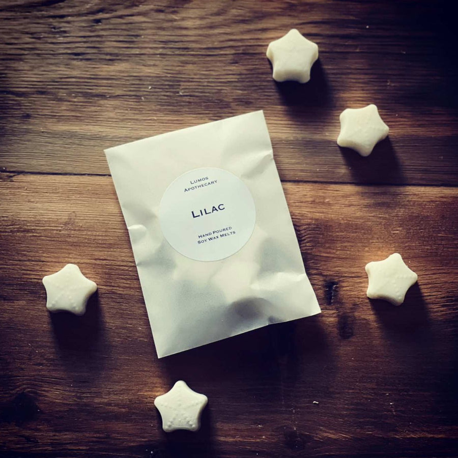 Lilac scented soy wax melts in a waxed bag surrounded by scattered wax melts on a wooden background