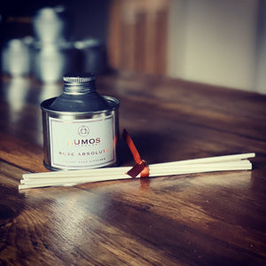 Rose Absolute Scented Reed Diffuser In Silver Bottle on wooden table - Lumos Apothecary. Soy Wax Candles UK