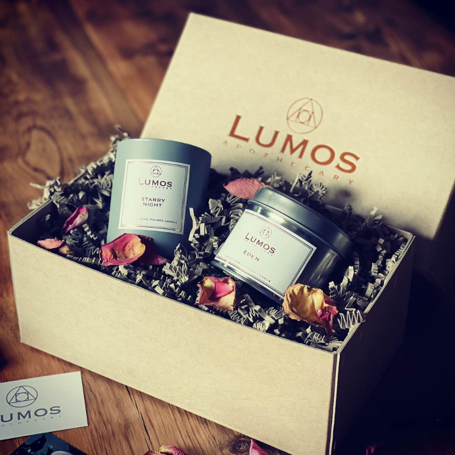Thanks Mum Soy Wax Candle Gift Set. Hand Stitched brown box with a starry night scented soy wax candle in a grey jar with an eden scented soy wax candle in silver tin sits inside with beautiful packaging and rose petals on wooden surface.