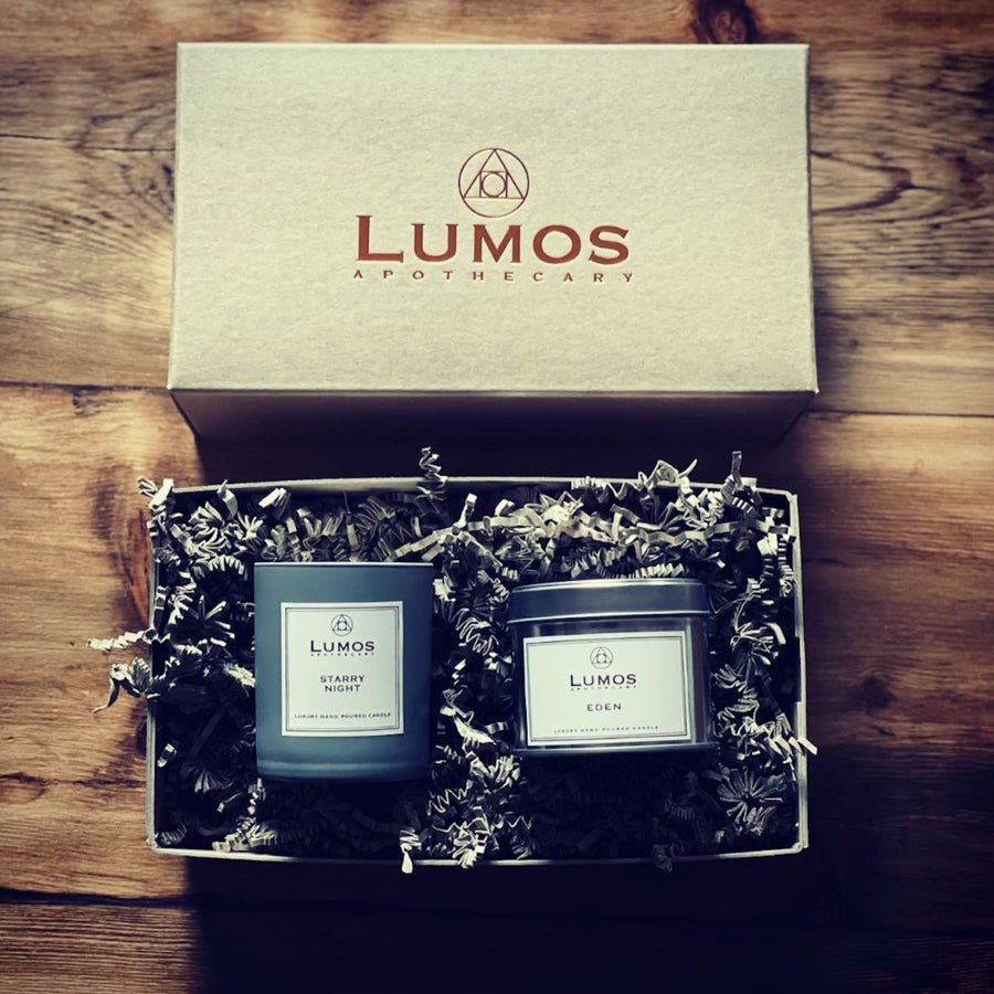 Thanks Mum Soy Wax Candle Gift Set. Hand Stitched brown box with a starry night scented soy wax candle in a grey jar with an eden scented soy wax candle in silver tin sits inside with beautiful packaging on wooden surface.