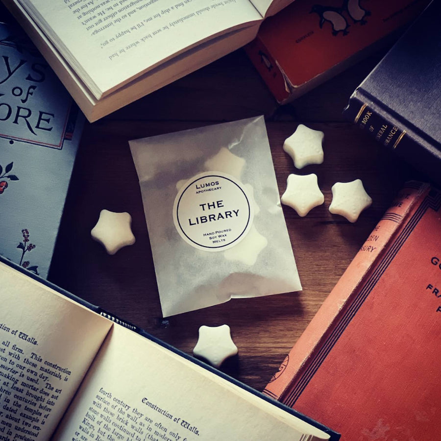 Leather Scented Soy Wax Melts in waxed bag on wooden table  surrounded by leather bound books. The Library Scented Soy Wax Melts