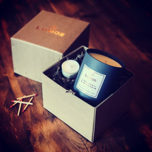 Luxury Hand Stitched Candle Gift Box. Hand Poured Lime Basil and Mandarin scented soy wax candle in grey jar inside a luxury gift box with zig-zag packaging on wooden surface.