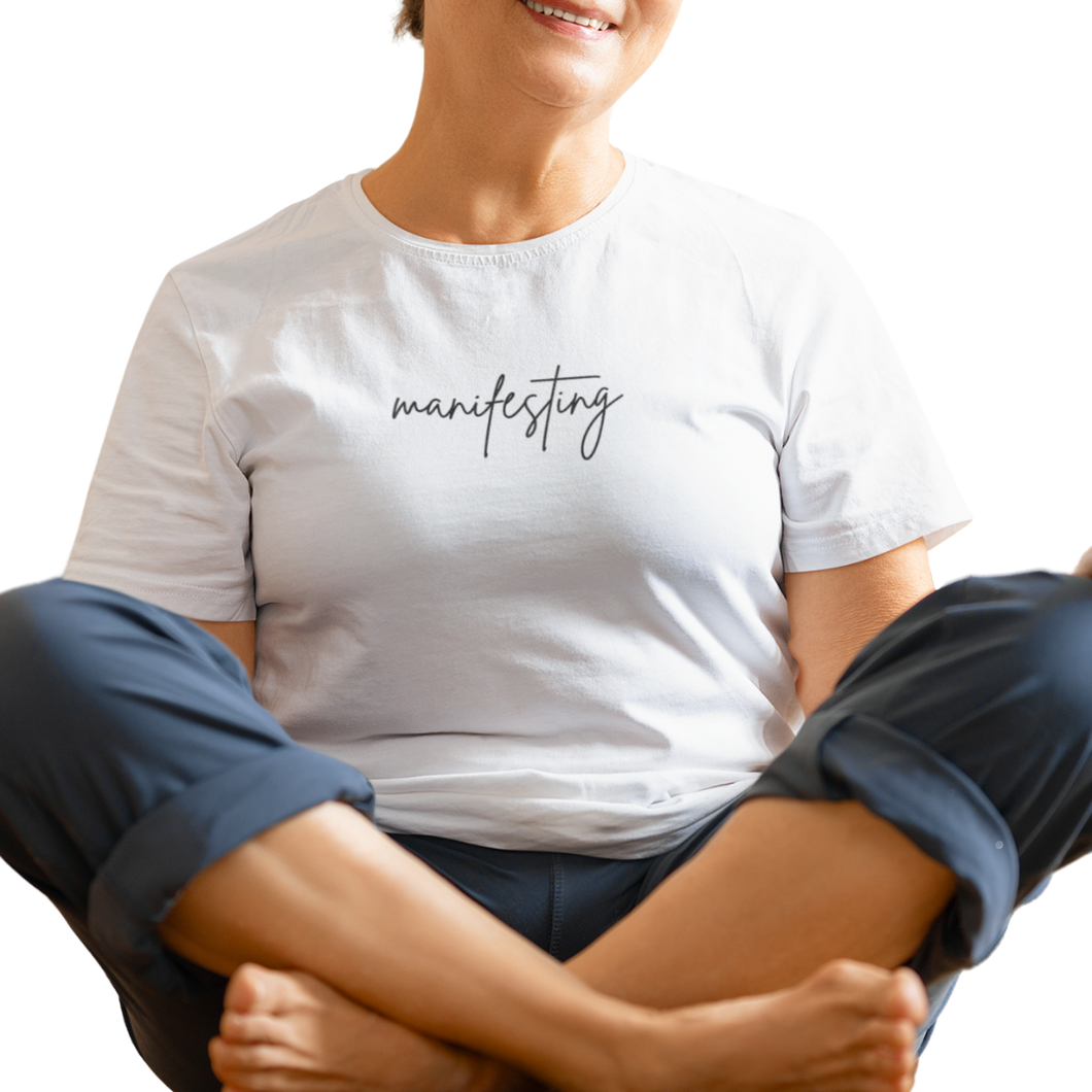 older woman sitting in lotus position wearing white manifesting tshirt