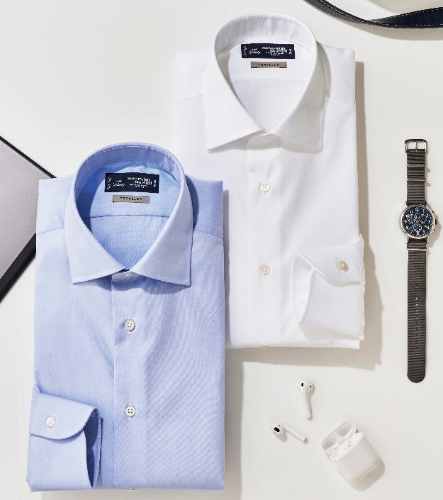 Two folded crisp blue and white dress shirts next to travel items