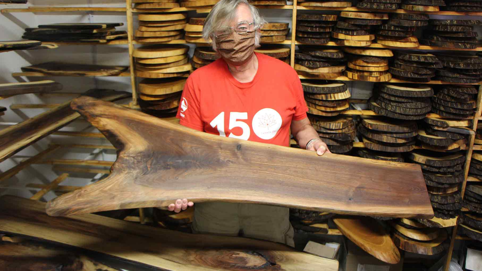 Bill Major in a face mask posing with one of his handcrafted grazing boards.