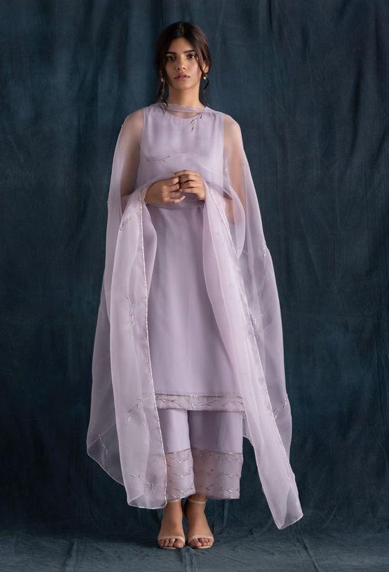 This set features a lilac kurta set includes a sleeveless lilac kurta and palazzo pants in georgette featuring silk organza panels embroidered with glass beads. It is paired with a lightly embellished