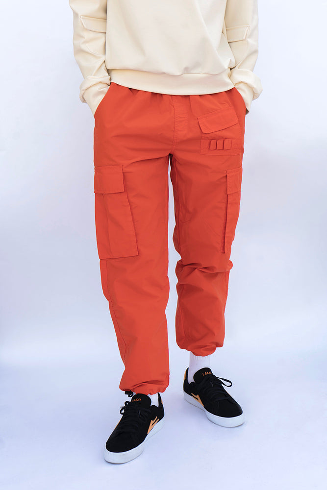 Man standing frontwards with orange cargo pants