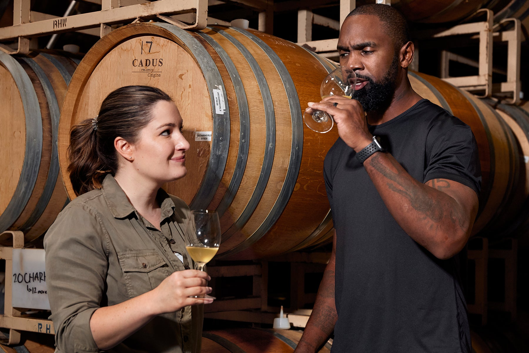 Intercept Winemaker Amanda Gorter and Charles Woodson sampling Chardonnay from barrels. Photo by Christina Schmidhofer.