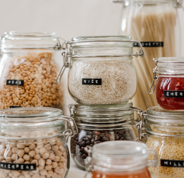 Small glass jars filled with different rice, peas, cherry jam, chickpeas, and spaghetti