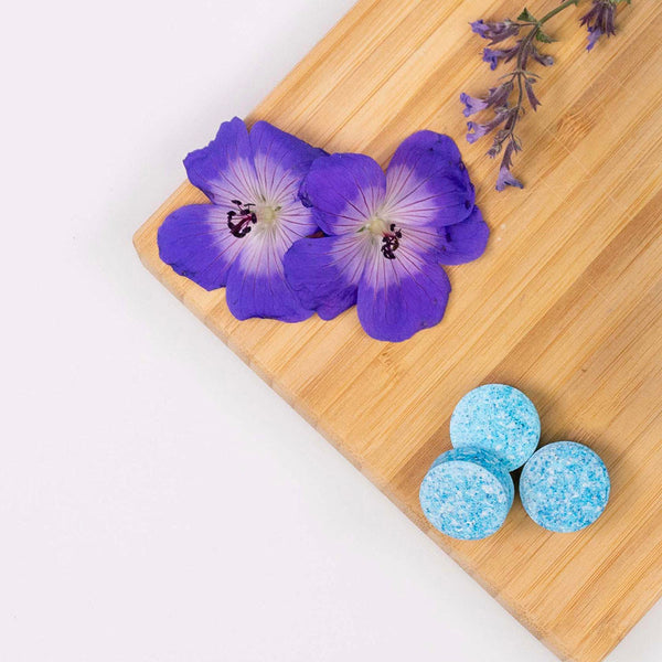 Skosh cleaning tablets and morning-glory flowers on a wooden cutting board