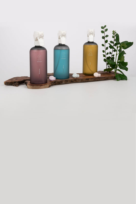 Reusable Skosh bottles made from 100% recycled plastic with spray-trigger on a wooden board