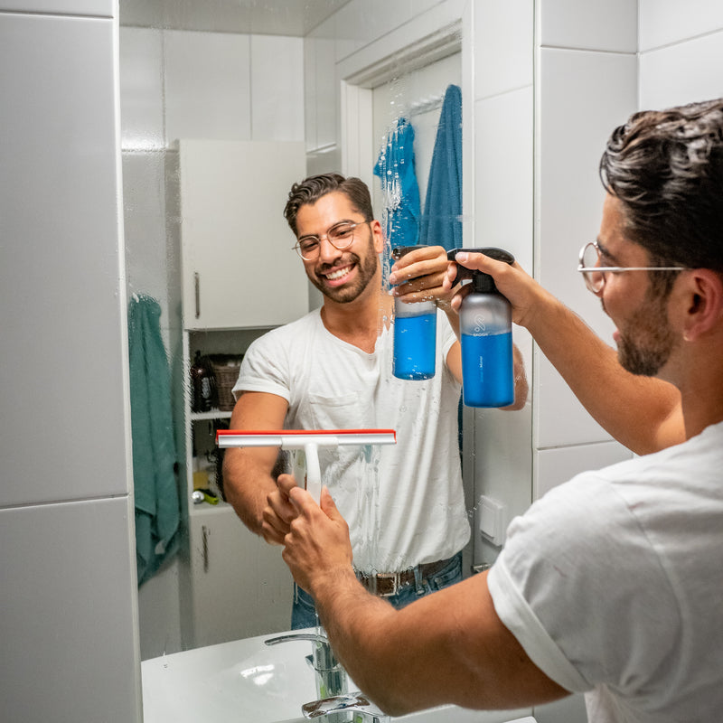 Person using Skosh's Glass&Window cleaner in the Bathroom, Sweden