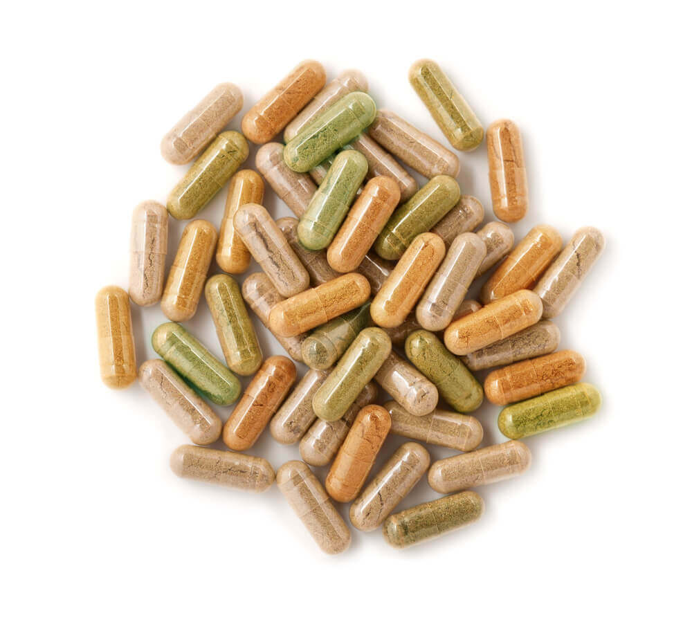 Closeup of a range of vegetarian capsules with different herbal remedies inside them