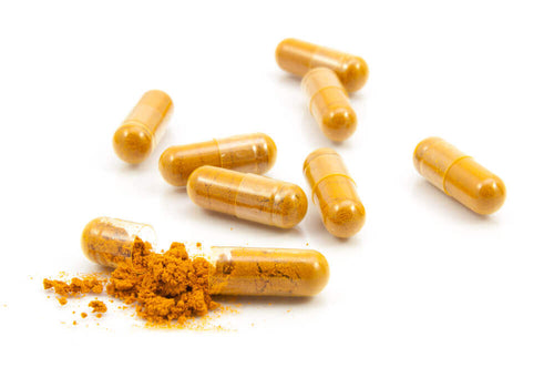 eight capsules filled with a yellow herbal supplement and one cracked open with the powder spilling out