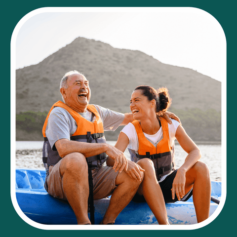 Father and daughter laughing on a boat on the side of a beautiful lake