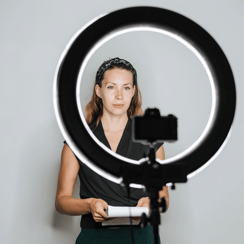 Woman using a professional ring light and tripod stand at home with her camera