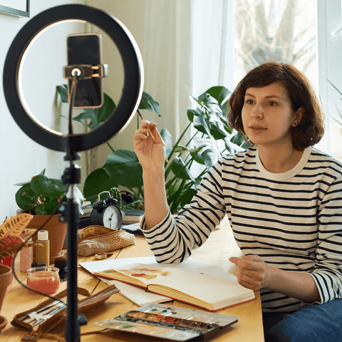 Woman teaching from home using her ring light and a phone