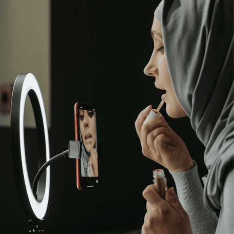 woman adding her makeup using her ring light tripod stand and phone