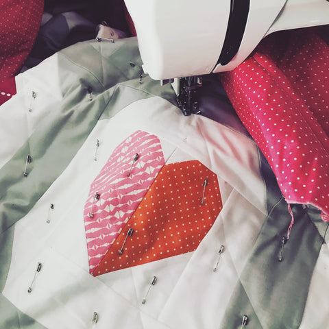 Close up of a quilt in progress. The quilt features a pink and orange heart inside a white chat bubble on a grey background. There are safety pins all over the quilt, and it is being fed through a Janome sewing machine.