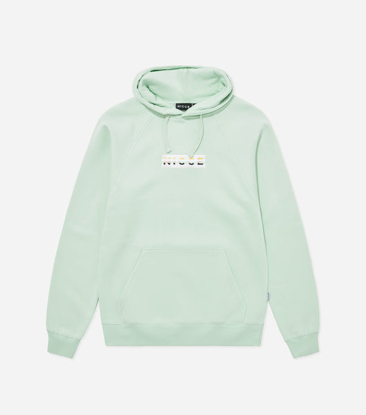 Hyam hood in mint. Featuring overhead hood, 90s style five colour box embroidered branding, front pouch pocket and raglan sleeve. Pair with matching joggers.