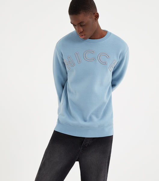 Bower sweatshirt in blue.. Features crew neck, relaxed fit, large embroidered chest logo. Pair with joggers or denim.