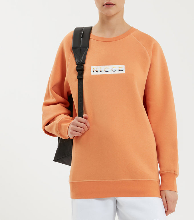 Hyam sweatshirt in coral. Featuring 90s five colour box embroidery logo, crew neck and raglan sleeve. Pair with joggers.  This is a unisex product, size down for true women's sizing.