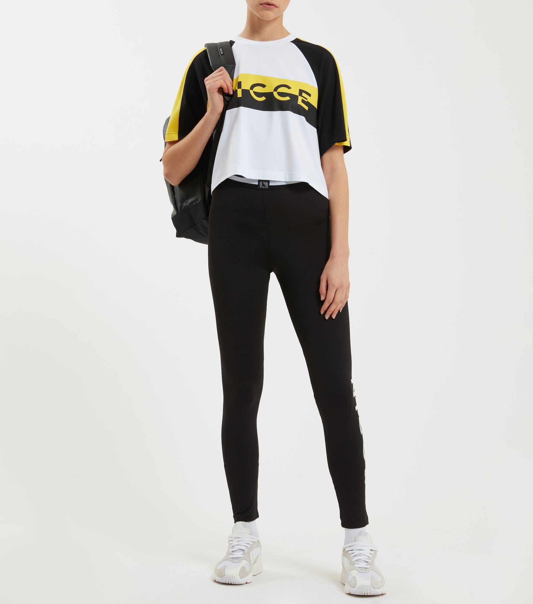 Acton t-shirt in white. Featuring crew neck, short raglan sleeves, cropped design and contrast split logo print in yellow and black. Pair with joggers or denim.
