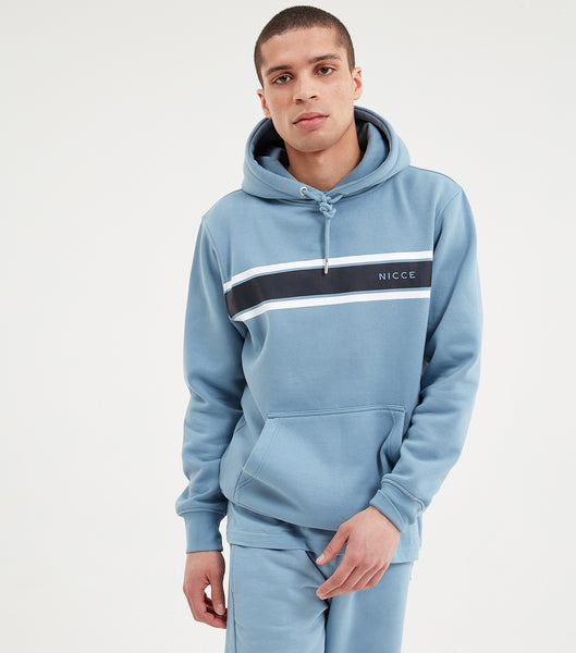 Varsity hood in blue. Featuring regular fit, overhead hood, front pouch, navy and white chest stripe design and printed logo. Pair with joggers or shorts.