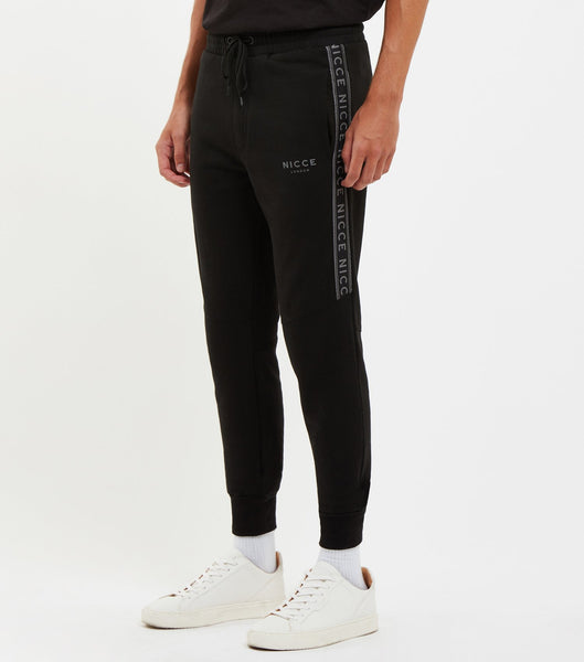 Nicce Blake Jog Pants in Black. Features skinny fit. elasticated drawstring waist with side pockets, cuffed ankles and signature branded thigh tape.
