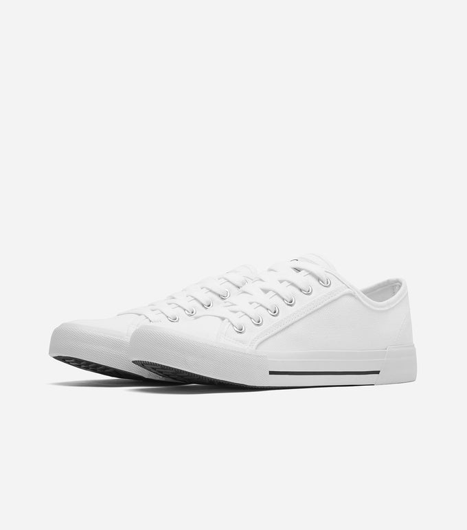 Kansas Trainer in white. Featuring canvas upper, tight woven, tear resistant fabric, lace up fastening, logo detail, chunky sole, moulded tread, clean with a damp cloth, low maintenance everyday footwear.