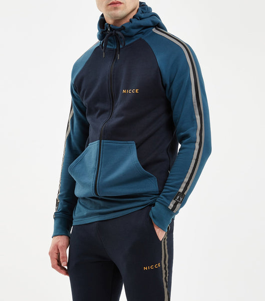 Bronco hood in majorca blue. Features multicoloured panelling in navy blue and yellow, printed logo, full zip, hood, down sleeves, arm taping detailing with elasticated cuff and waistband. Pair with Bronco joggers.
