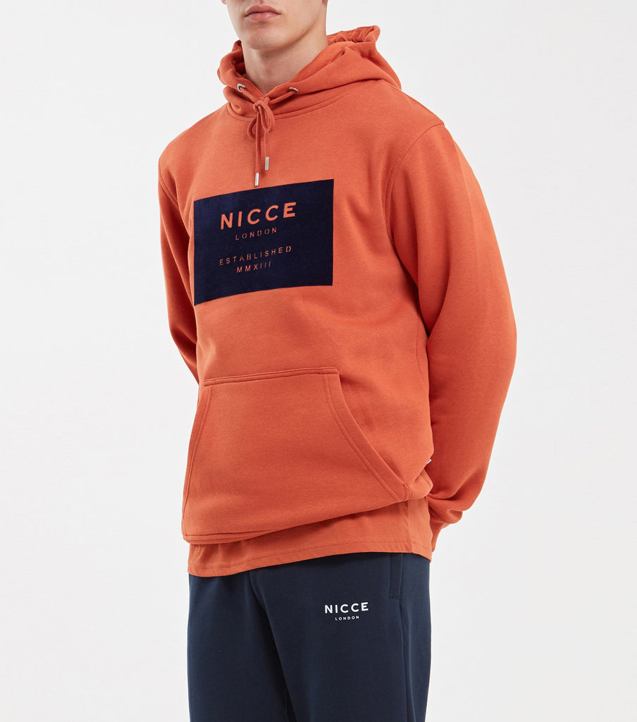 MMXIII hood in burnt orange. Features large front chest box branding in flock, front pouch, hood with drawstrings, elasticated cuff and hem. Pair with joggers.