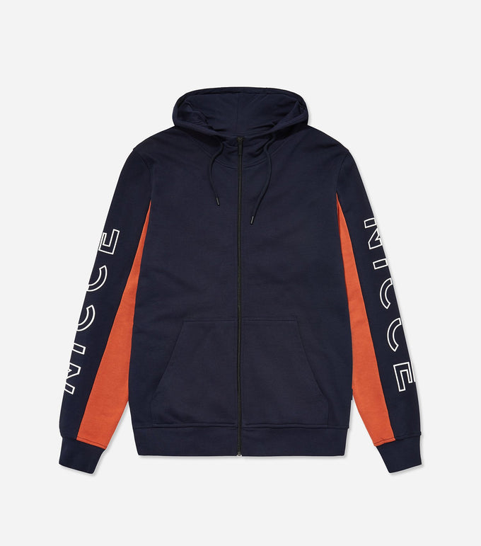 Cerium hood in Deep Navy/Burnt Ochre. Features zip through hood with drawstrings, full zip, arm branding logo, pocket pouch and contrast paneling in orange. Pair with joggers.