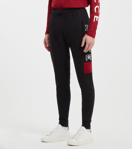Cerium jogger in black. Features skinny fit, contrasting colour panelling in merlot, large thigh nicce branding, two pockets, elasticated ankle cuffs and waistband with drawcord. Pair with hood.