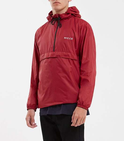 Core cagoule in merlot. Features light weight material, overhead hood, chest branding, two side entry pockets. Pair with joggers.