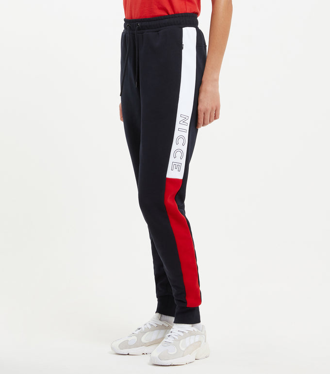 Conti joggers in navy. Features skinny fit design, colour block design in navy, red and white, left leg printed logo, elasticated drawstring waistband.