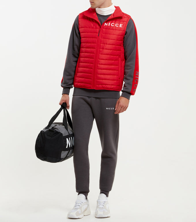 Vail gilet in red. Designed as a layering piece with extra padding to keep you warm and insulated. Features full zip, ripstop fabric, high neck, warm insulated padding, block chest logo and chest logo. Pair with joggers.