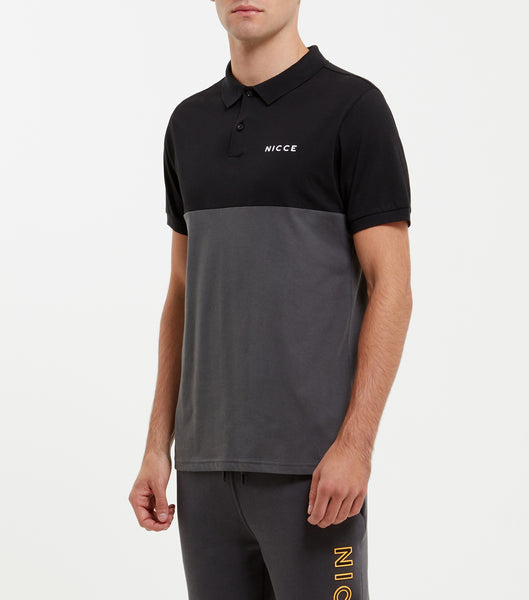Silverton polo in coal. Featuring colour paneling in coal and black, printed chest branding, classic polo shirt shaping, collar and button up. Pair with joggers.