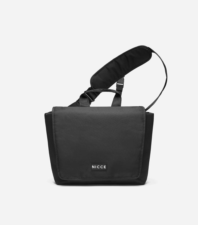 Verdo Messenger bag in black. Features messenger design, NICCE contrast rubber logo, printed repeat branded lining, adjustable padded strap for easy wearing, branded grosgrain and buckle.  Details:  Black  Messenger Bag  100% Polyester