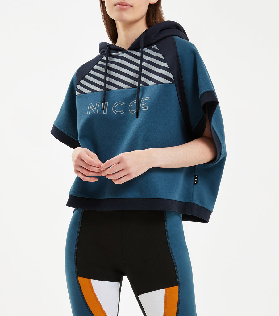 Boxer hood in majorca blue. Featuring crop fit, contrast hood with rib details, illusion stripe chest print and raised rubber keyline logo. Pair with NICCE Game leggings.