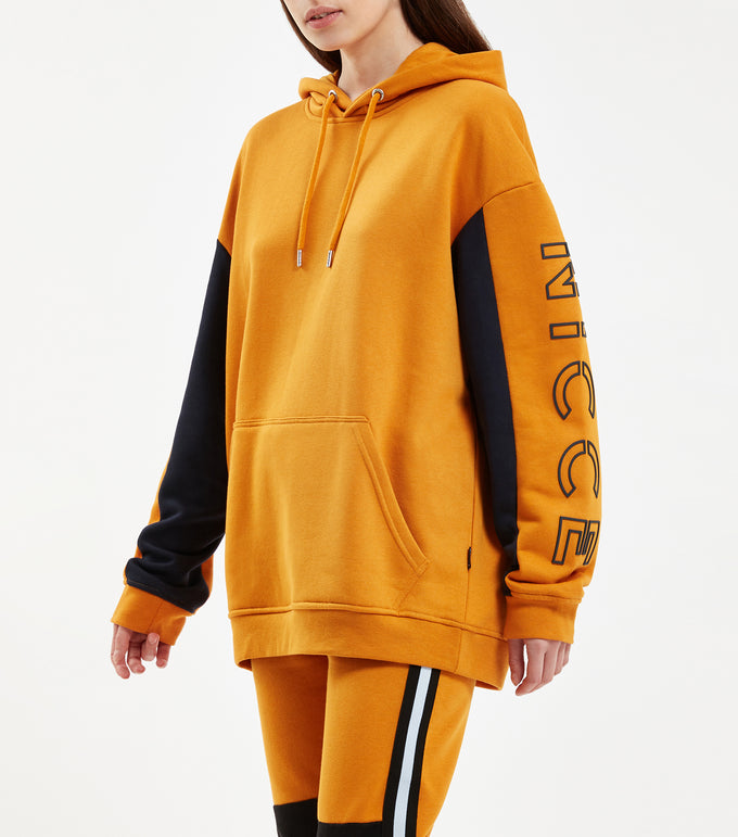 Contrast hood in golden yellow. Features oversize fit with undersleeve contrast colour panel, kangaroo pouch, cotton drawcord with branded metal eyelets and large keyline split raised rubberised logo on sleeve. Pair with NICCE vivid joggers.