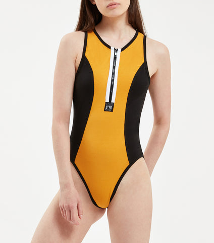 "Tron bodysuit in black and golden yellow. Features high cut leg fit, Front zip opening with contour seam panels, sports flatlock thread detailing, contrasting edge binding and branded with woven ""N"" badge. Pair with NICCE Court joggers."