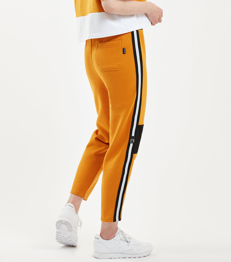 "Vivid jogger in golden yellow. Features duo black woven ""N' badges, duo coloured stripe waistband with cotton drawcords, branded metal hardware, single back patch pocket, two colour stripe elasticated tape at side seams, tapered fit with cropped ankle length and contrasting knee panels. Pair with NICCE Contrast hood."