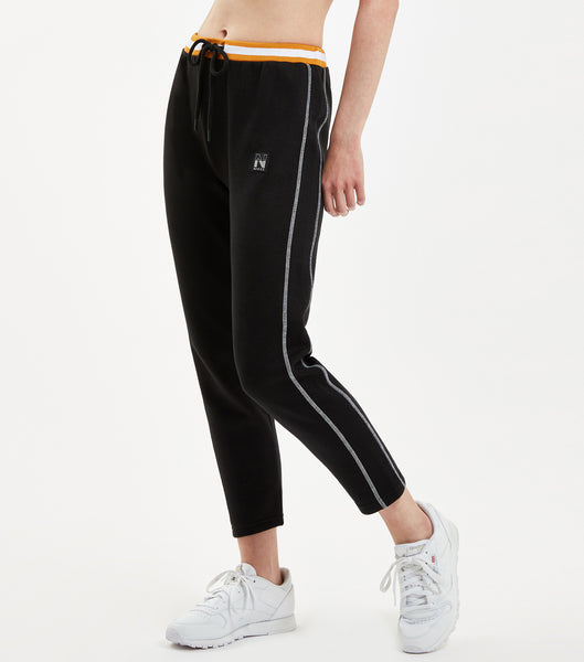 "Court jogger in black. Features tapered fit, cropped ankle length with open hem, contrasting white flatlock thread seams, duo colour stripe rib waistband with cotton drawcord, branded metal hardware, single patch pocket and ""N"" bage branding. Pair with NICCE Slice sweat."