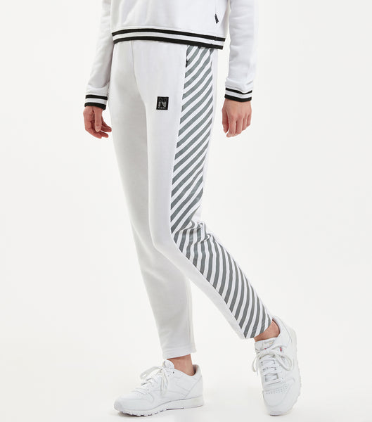 "Illusion jogger in white. Features cropped ankle, tapered slim fit, with bold illusion stripe print at side seams, duo colour stripe ribbed waistband with cotton drawcord, branded metal hardware and ""N"" badge branding. Pair with NICCE Illusion zip sweat."