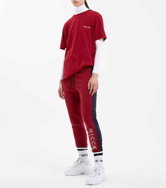 Rival jogger in merlot. Featuring tapered skinny joggers, cropped ankle length with two colour cuff rib, contrasting side seam panels, small raised rubber keyline logo at the hem edge, two colour rib waistband with cotton drawcord and black branded metal hardware. Pair with hood.