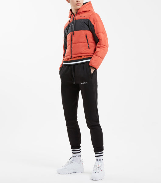 Flash crop puffa jacket in burnt orange. Features quilted fabric, hood, under sleeve panelling in black, zip pockets, front classic small heatpress reflective logo and black rubberised logo zip puller.