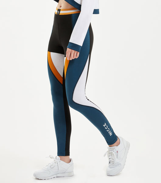 "Game leggings in majorca blue. Features contrast colour multi panels, high waisted fit, with sports flat lock seams, small print logo at hem, elasticated stripe colour tape at waist and ""N"" badge branding. Pair with NICCE Tidal sweat tee."